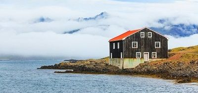 Lonely Black Wooden House at coastline in East Iceland.